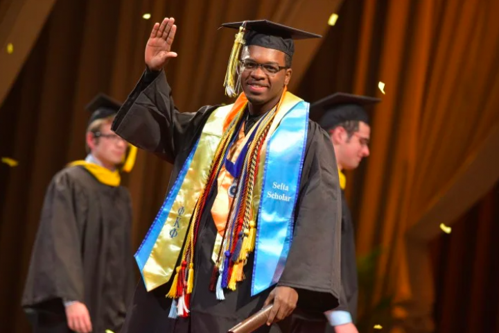 J. Gabriel walks across stage in cap and gown, waving to audience during graduation