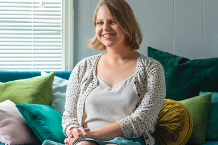 Erin Beal poses for camera, sitting on couch