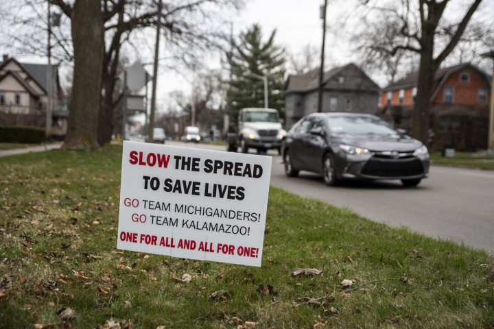 """""""Slow the spread to save lives. Go Team Michiganders! Go team Kalamazoo! One for all and all for one"""" sign outside on lawn with cars driving in background"""