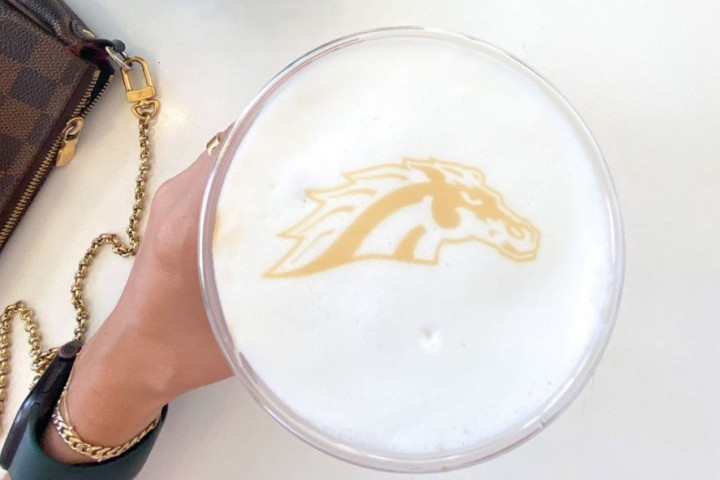 A Bronco head in the foam of a cup of coffee.