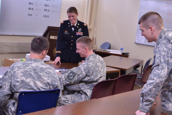 Military dressed individuals inside a classroom