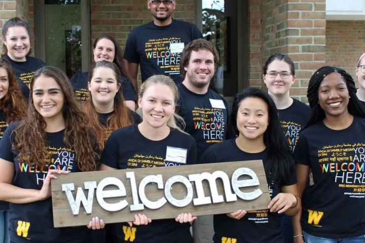 """Students holding a """"Welcome"""" sign"""