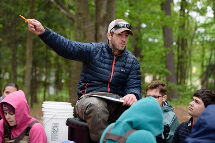Dr. Devin Bloom working with young adults in an outdoor setting