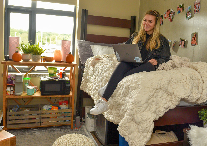 Student sitting on bed in residence hall