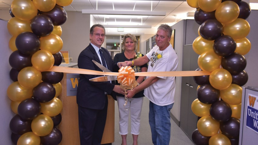 Photo of Dr. Bret Wagner, Renae and Fred Rauker cutting ribbon