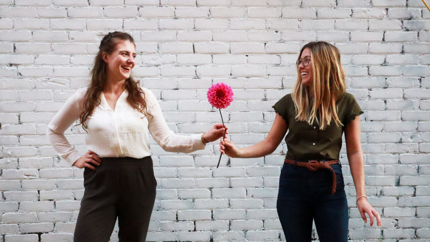 Ariel and Anezka in front of a white wall holding a large pink flower
