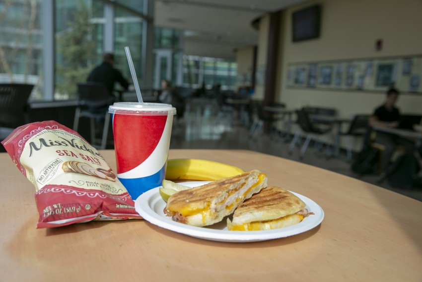 Grilled cheese sandwich with chips and a drink