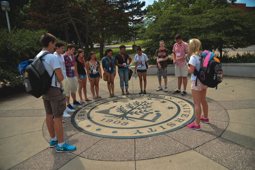 Students outside standing over the Western seal