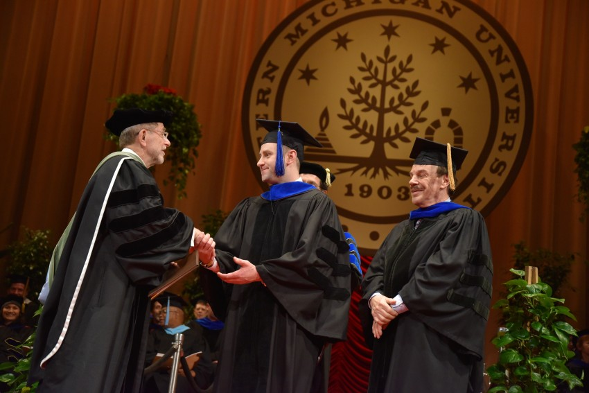 President Dunn shaking hands with a doctoral student on stage at graduation