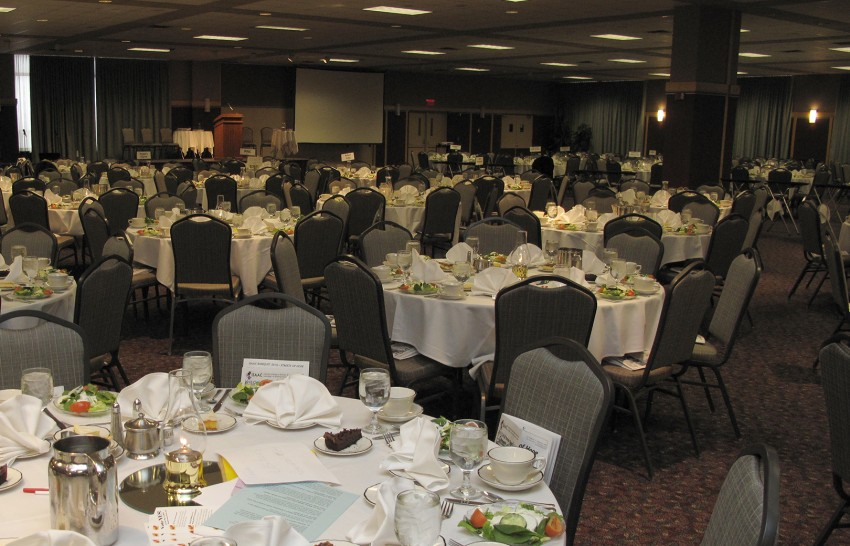 Large room with tables decorated for a meeting.