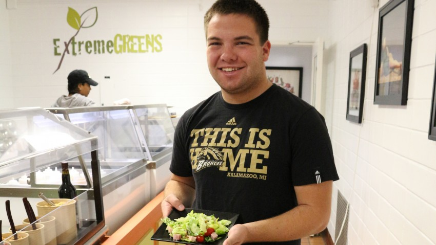 Male student with a salad at Extreme Greens in Burnham dining