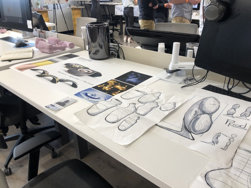 Product design sophomore studio workstation with sketches and prototypes on table.