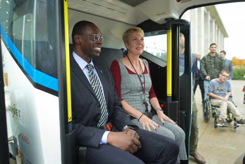 Lieutenant Governor Garlon Gilchrist sits next to Jean Ruestman as they get a ride inside the autonomous shuttle.