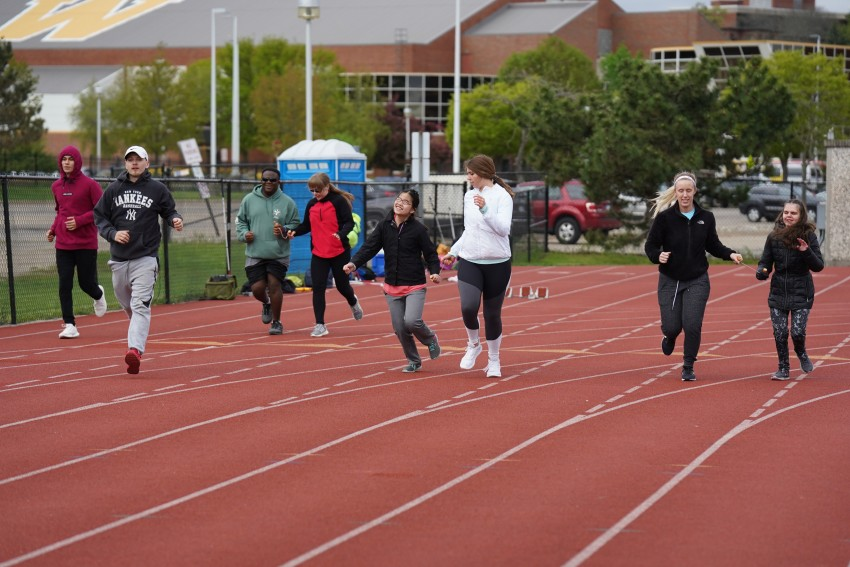 Visually impaired athletes and camp counselors run on a track.