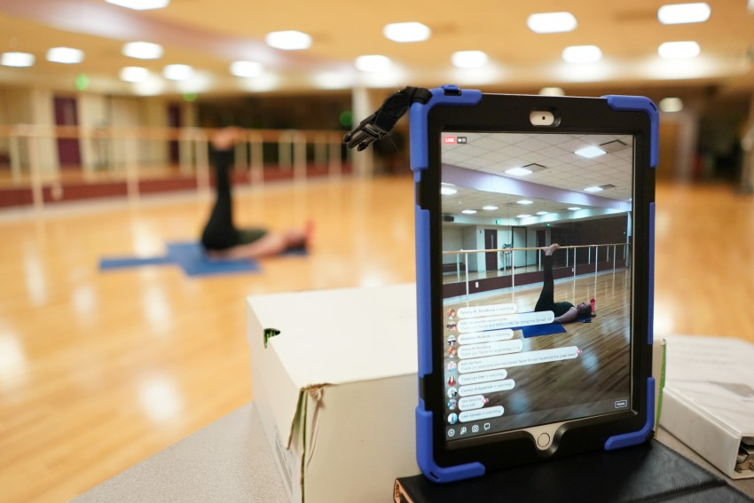 A yoga instructor livestreams a class on her ipad.
