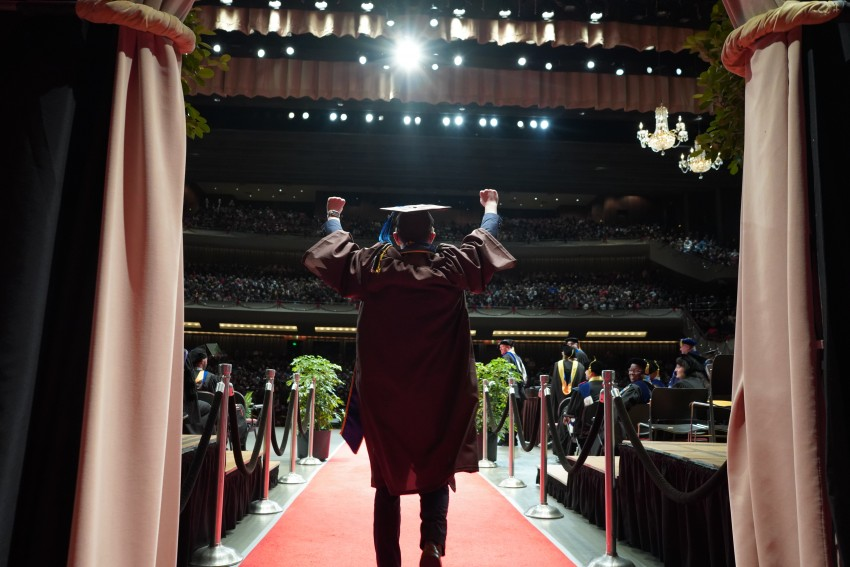 A graduate walks onto the commencement stage raising his arms in accomplishment.