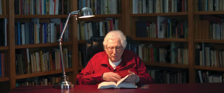 Siebert reads a book at the desk in his study.