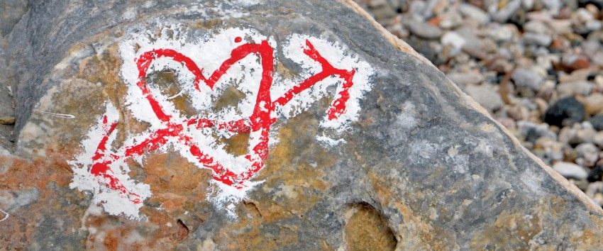 A heart with an arrow through it is drawn on a rock.