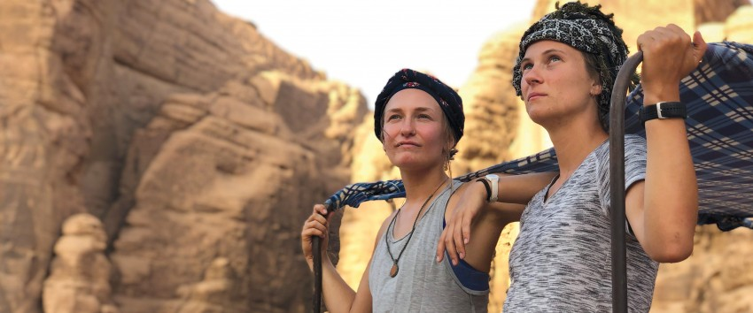 Two young women are photographed in the desert looking off into the distance.