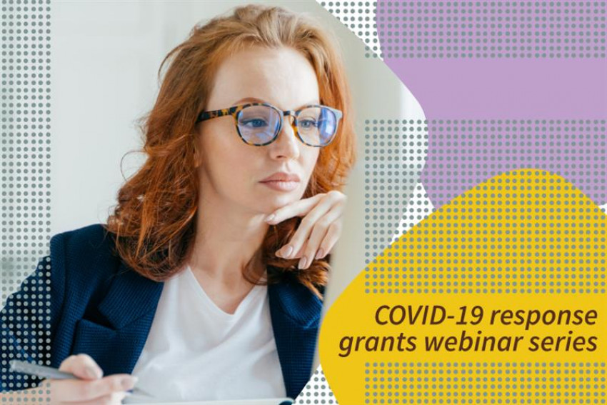 "Woman sitting at desk holding pen in hand. ""COVID-19 response grants webinar series"""