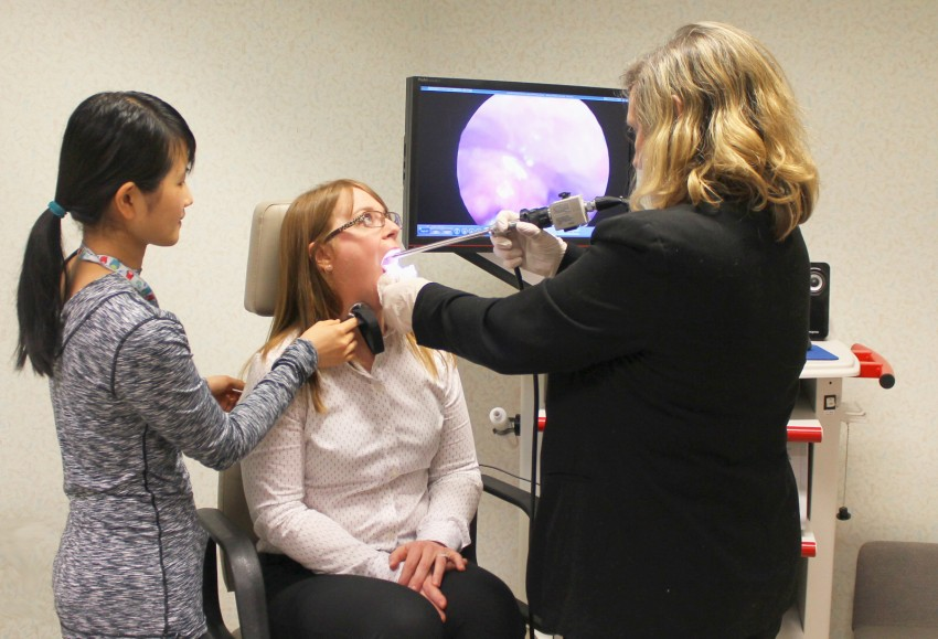 A womans vocal folds are examined.