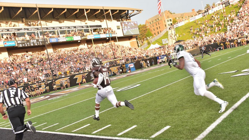 Photo of a WMU football player running toward the end zone.