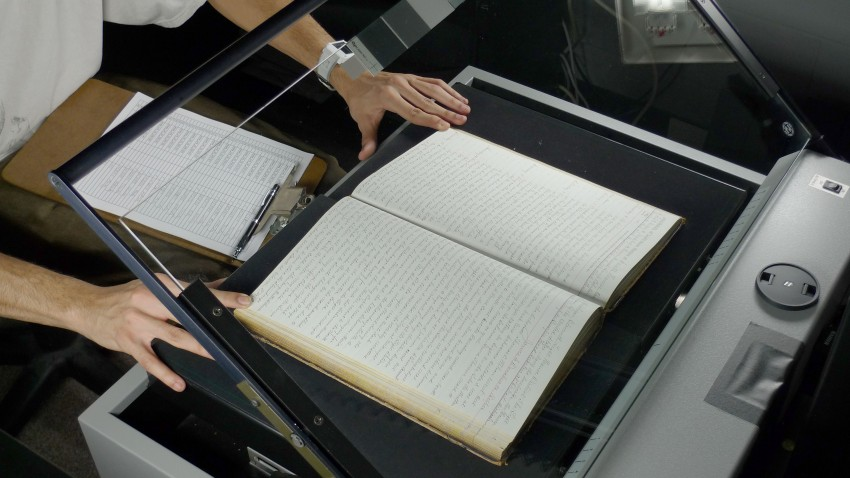 Photo of a lighthouse logbook on a scanner.