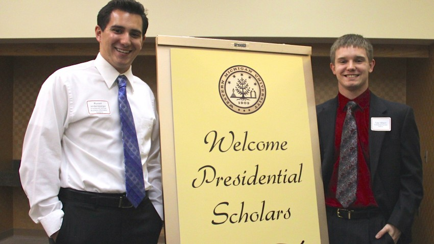 Photo of two WMU students by a Presidential Scholars sign.