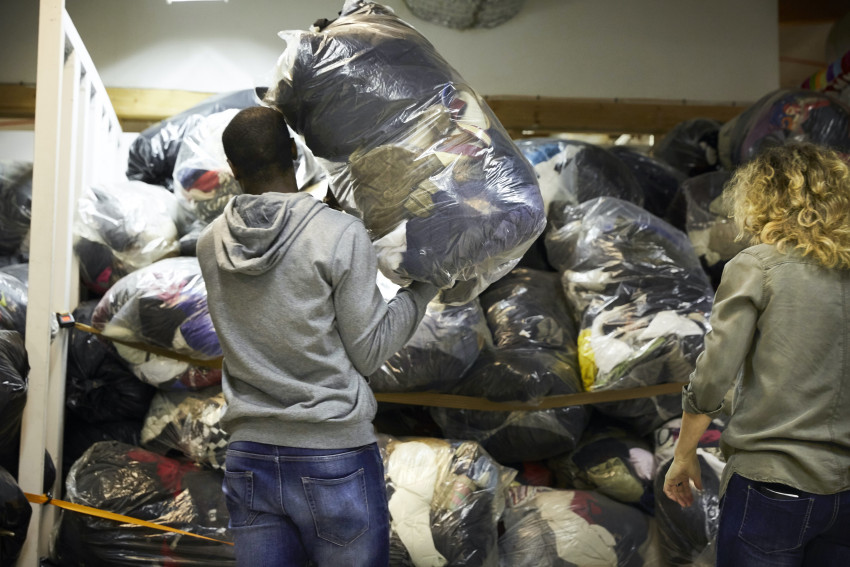 A man loads a bag of clothes onto a shelf of donations.