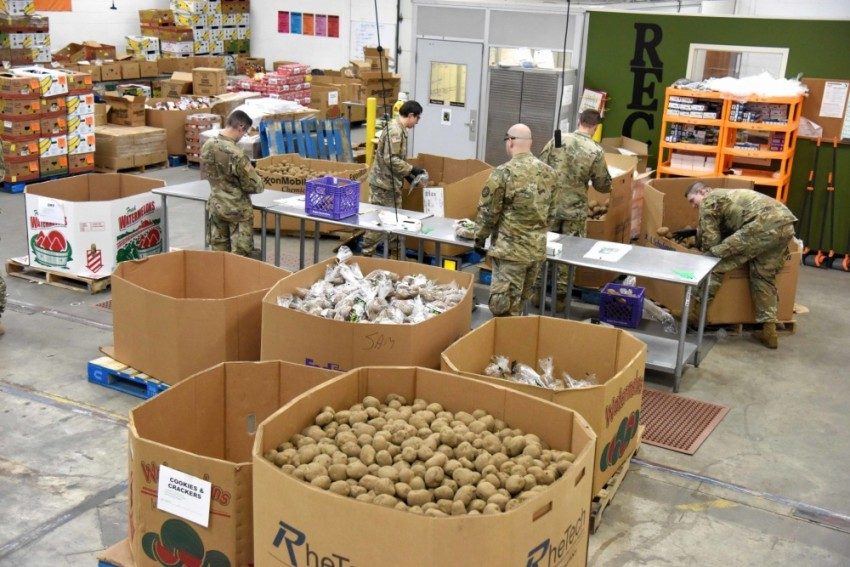 National Guardsmen pack boxes of food in a warehouse.