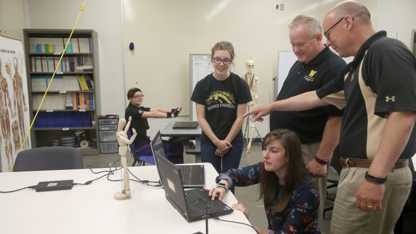 Photo of student and faculty researchers at the College of Engineering looking at laptops.