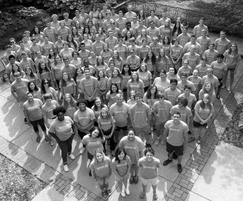 A black and white photo of a group of about 120 high school music camp students both male and female posing for a group picture in matching t-shirts.
