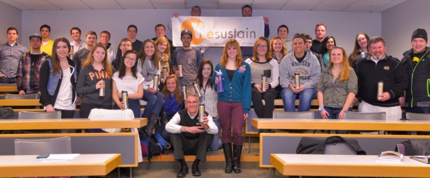 A classroom of students holding Sustainability mugs