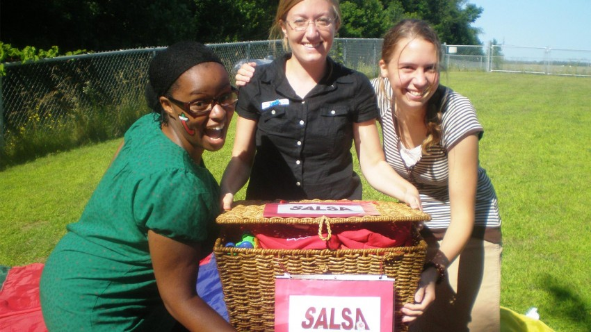 Three women presenting a basket of salsa.