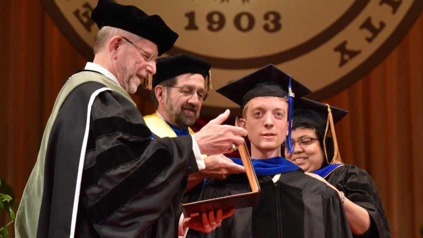 Alexander Houser, Ph.D. receiving his degree from former President John Dunn