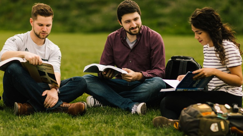 Photo of WMU students sitting outside with books.