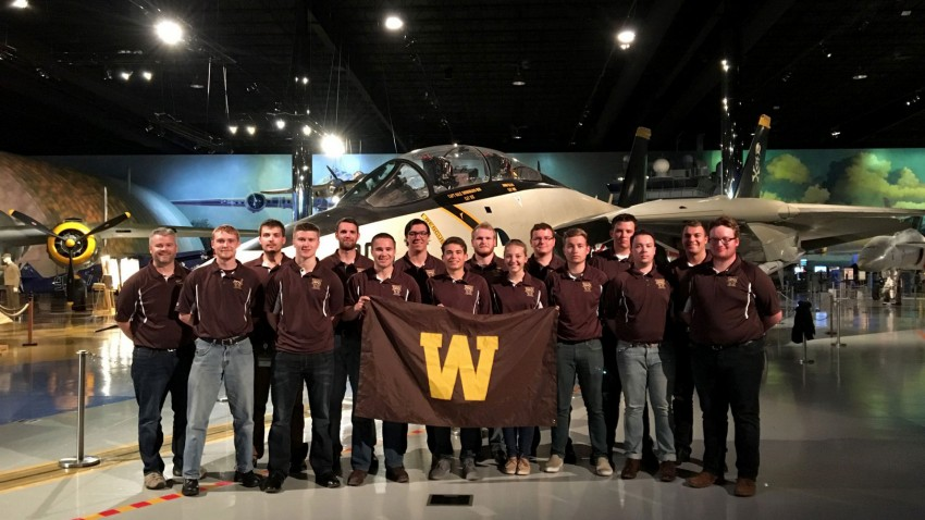 Members of the 2017 regional Sky Broncos team standing in a hangar in front of an airplane holding a W flag.