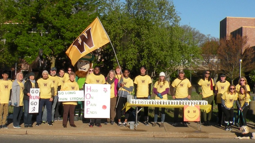 Volunteers pose with a WMU flag at a Kalamazoo Marathon Excitement Zone on campus.