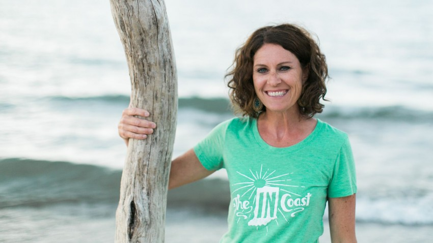 Jennifer Soffin stands on the shoreline wearing a mint green The IN Coast T-shirt.