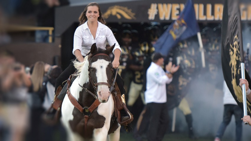 Emily Stewart rides a horse on the field of WMU's Waldo Stadium. The Bronco football team gets ready to storm the field behind her.