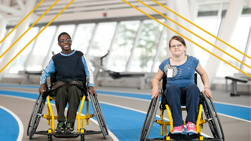 Two disabled youth in wheelchairs push themselves around an indoor track.