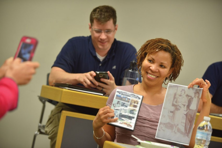 A student holds up pictures while someone takes a photo with a cell phone.