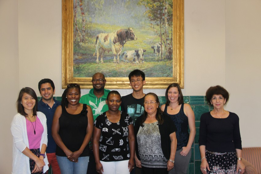 Eight students and Dr. Di Pierro stand for a photo in front of the fireplace of Walwood Commons. Behind them above the green ceramic tiles of the fireplace is a large painting featuring three cows in a field as seen through a break in the woods.