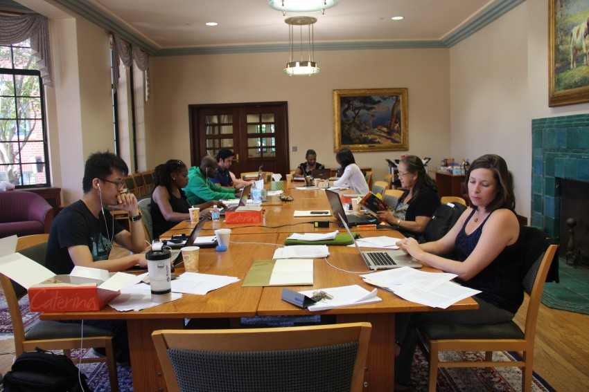 Nine students are seated around a large table in Walwood Commons, each appears to be engaged in studious activity such as typing on their laptop, reading articles, or examining the text of a book.