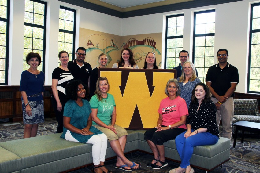 2017 Dissertation Cafe participants with Dr. Christine Byrd-Jacobs, Acting Dean of the Graduate College and Dr. Di Pierro, Program Manager for Graduate Research and Retention. A group of eleven diverse students surround a large gold W which pronounces the WMU brand. Walwood Hall, where the Graduate College is located, has been recently renovated with new carpet and furniture to host small and large groups. The original murals from 1939 can be seen behind the students, while the tall narrow windows frame a view of East Campus with its many trees and classic buildings.