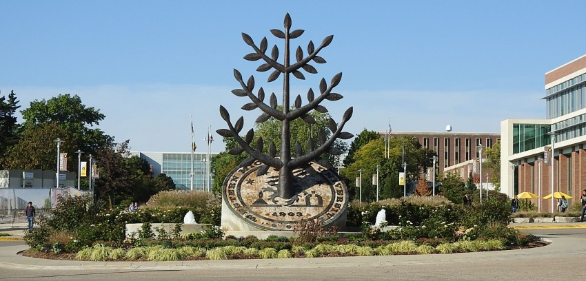 This image is a photo of a sculpture titled The Tree of Growth that stands in the trun around section of the drive near Sangren Hall. The sculpture has a large circular base of concrete with a 45 degree angle cut across the top where the Western Michigan University seal is displayed in raised bronze relief. The center element, the tree of knowlege breaks free from the confines of the traditional seal and springs upwards seventeen feet into the air to symbolize the primary mission of the university.