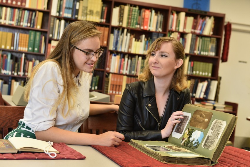 Two student employees in Special Collections reviewing a World War 2 scrapbook.