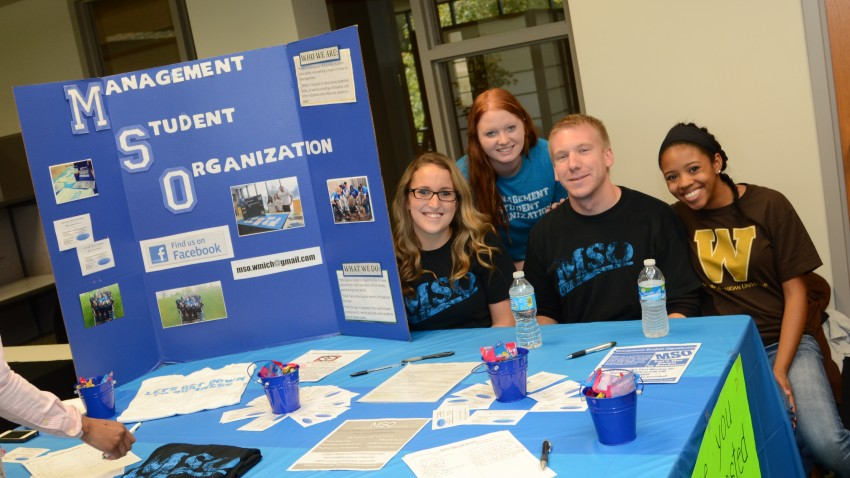 Photo of Management Student Organization display with three students