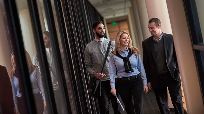 three business professionals walking down a hall