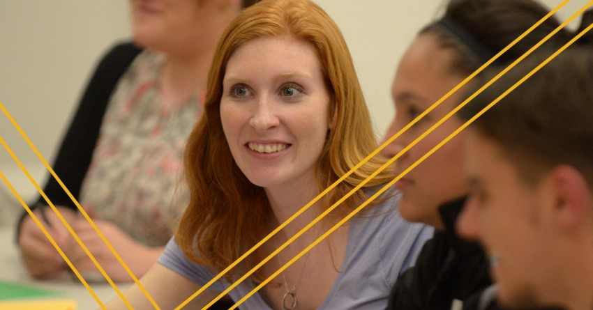 focused red-headed woman staring intently. other students in the foreground and background gaussian blurred. decorative gold stripes overlaid.